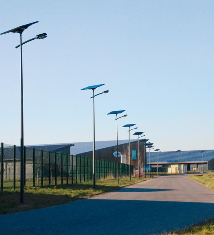 Solar LED streetlights running alongside a commercial area road