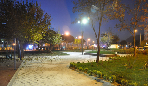 A playground in a Turkish parc by night lighted by solar LED street lamps