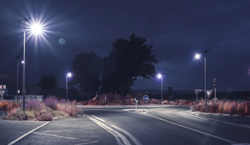 A traffic circle in Cruscades at dawn illuminated by Fonroche Lighting's solar streetlights