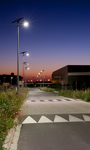 A commercial area in France at dusk lighted by solar LED street lamp posts